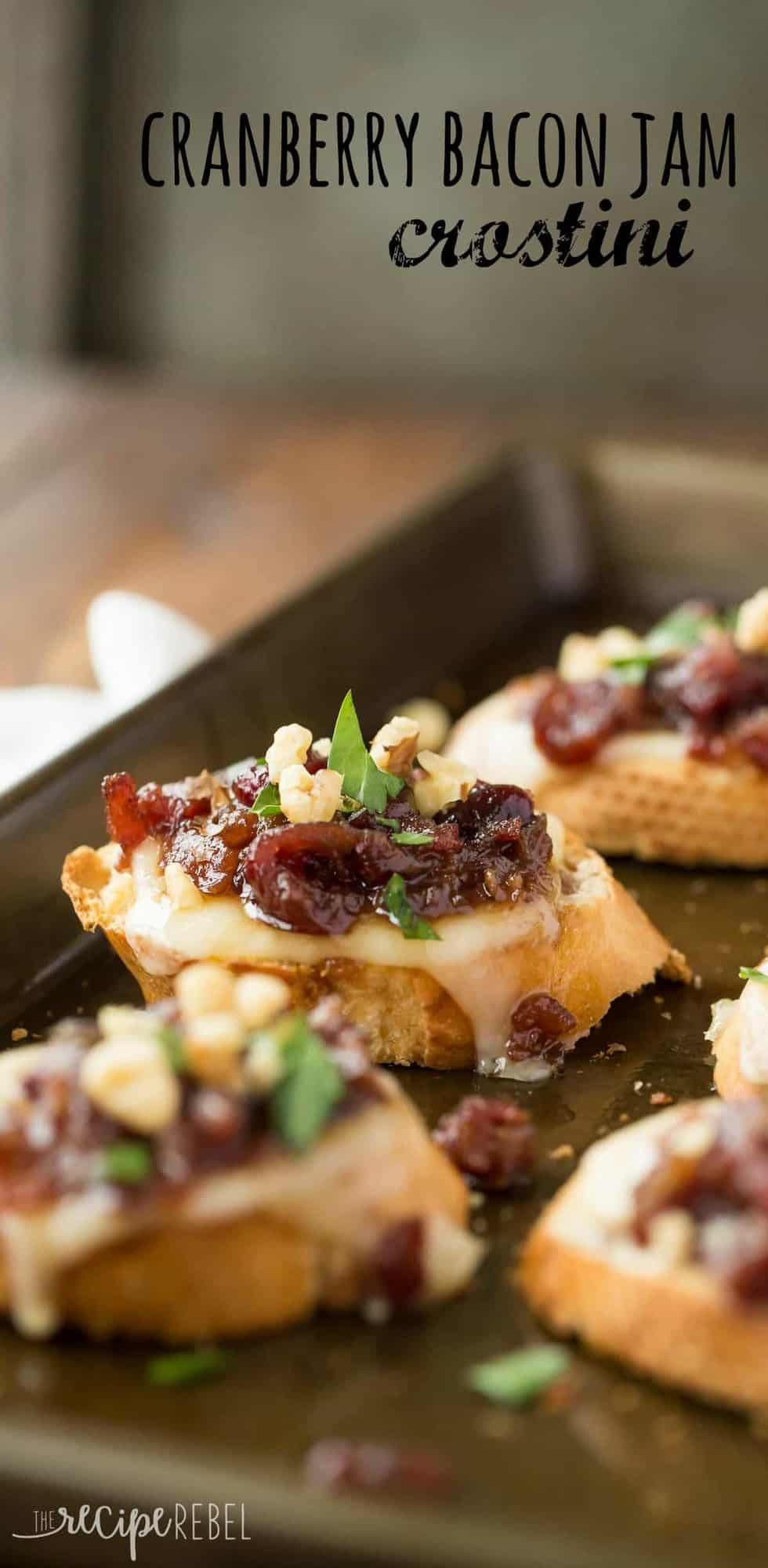 cranberry bacon jam crostini on a sliced baguette with walnuts and parsley lined up on a sheet pan