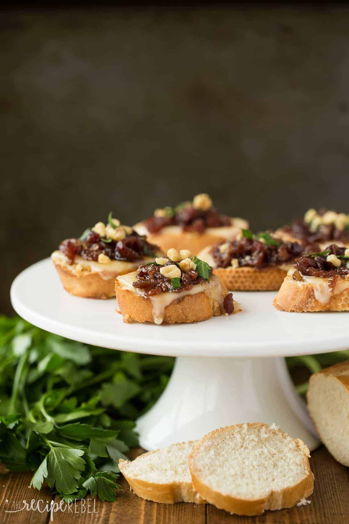white cake plate with cranberry bacon jam crostini on op and fresh parsley on the side