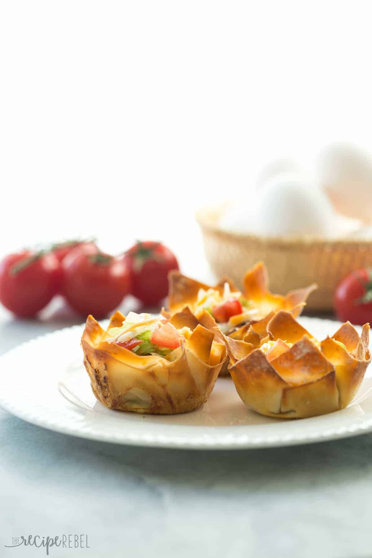 mini mexican wonton quiche with tomatoes and whole eggs in the background