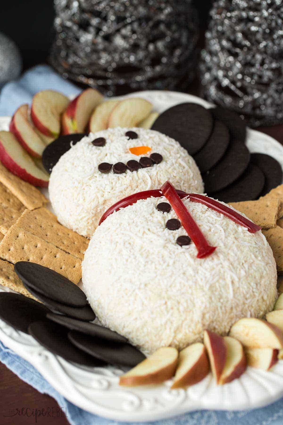 white chocolate snow man cheese ball on white platte with wafer cookies graham crackers and apple slices