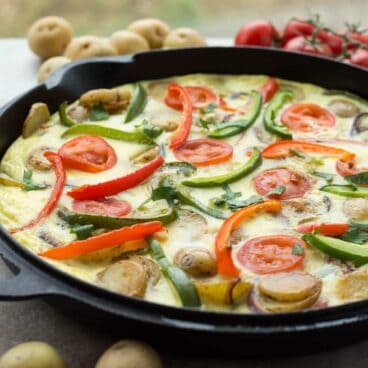 This Spanish Tortilla is really just a Spanish omelette -- made with sliced potatoes, onions and peppers fried together before being topped with beaten eggs and baked. It's perfect festive holiday breakfast!