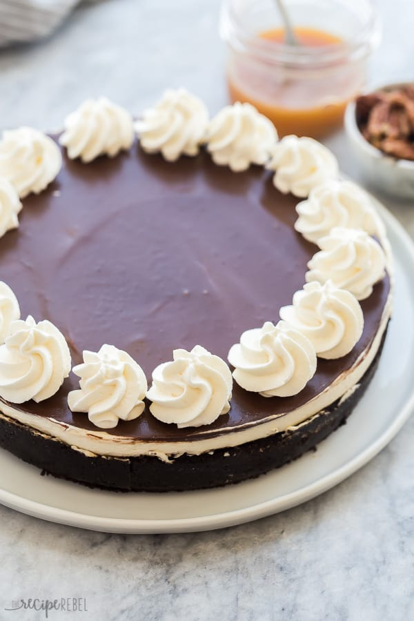 no bake turtle cheesecake whole with chocolate ganache and whipped cream