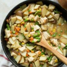 30 minute skillet chicken stew in large black skillet with wooden spoon scooping