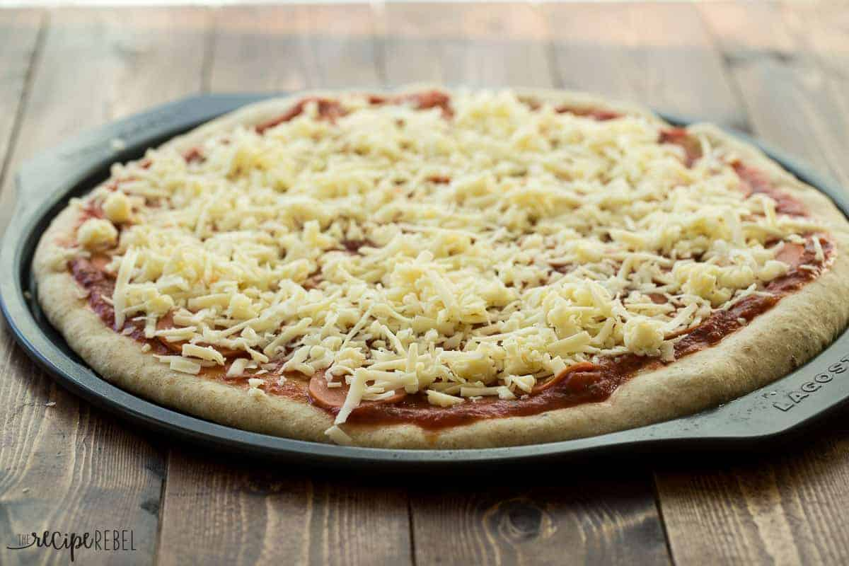 par baked pizza crust with tomato sauce pepperoni and cheese