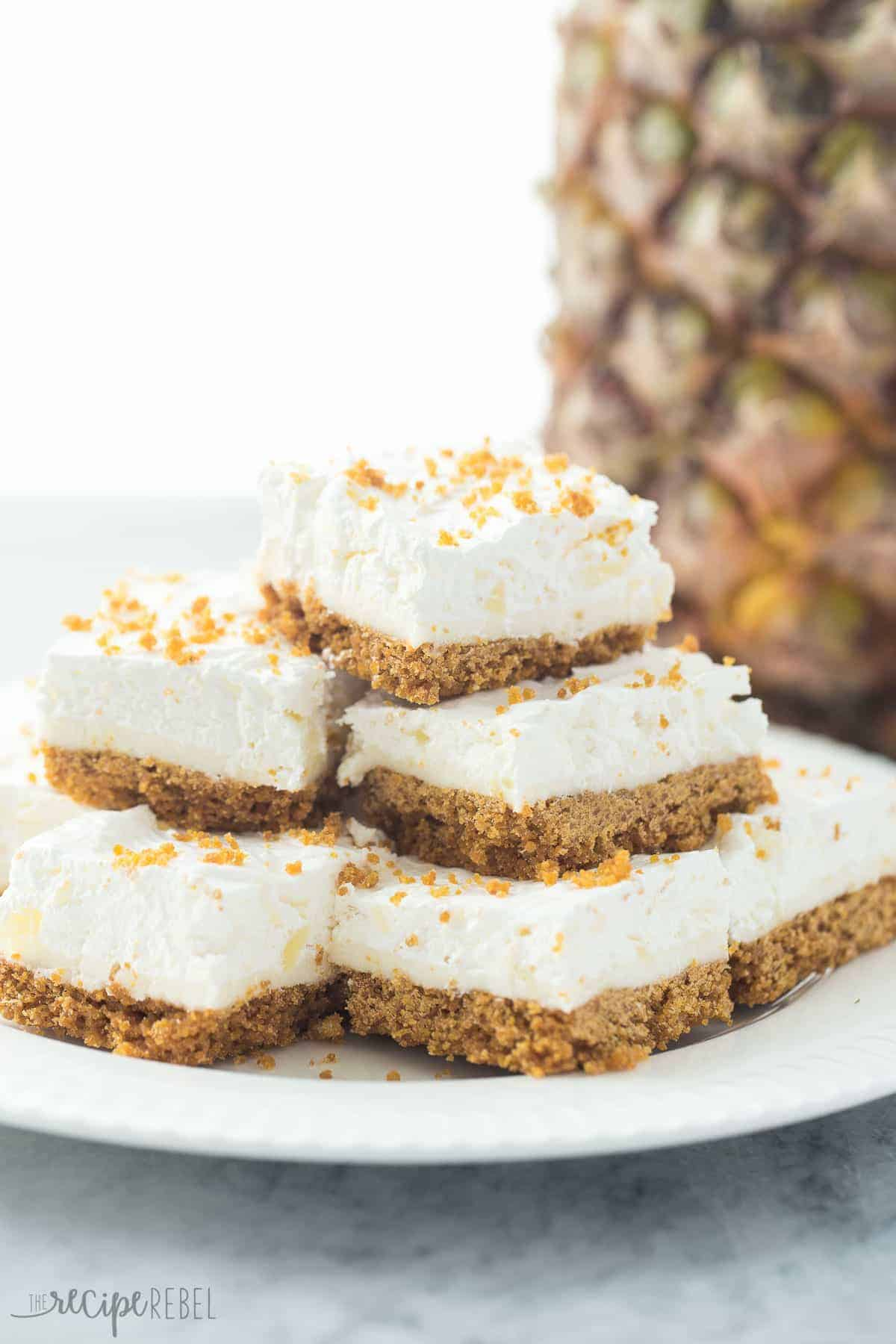 stack of no bake pineapple squares on white plate with whole pineapple behind
