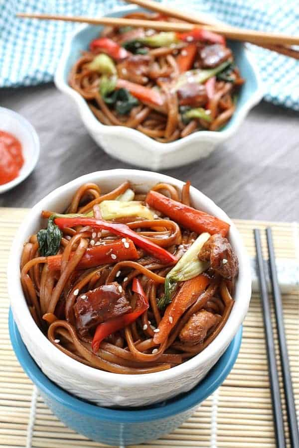 slow cooker chicken lo mein in white bowl with peppers and chopsticks on the side
