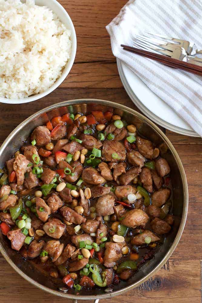 kung pao chicken in skillet with peanuts and green onions