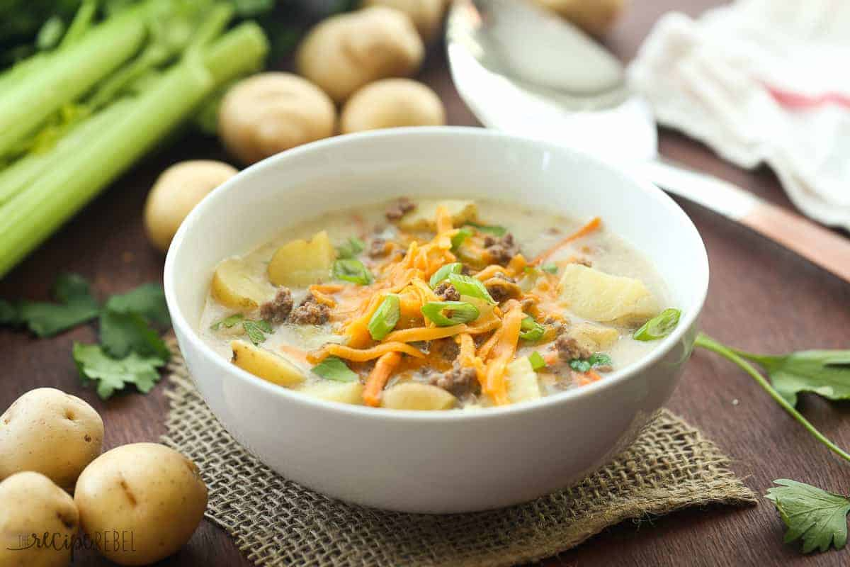 white bowl with cheeseburger soup and potatoes and celery in the background