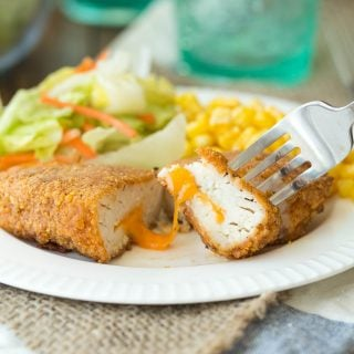 This Nacho Cheese Stuffed Oven Fried Chicken is stuffed with cheddar cheese and coated in a (from scratch -- no weird ingredients!) nacho flavored coating, and then oven fried to crispy perfection!
