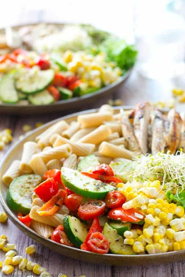 grilled chicken veggie pasta bowls close up with corn zucchini tomatoes and chicken
