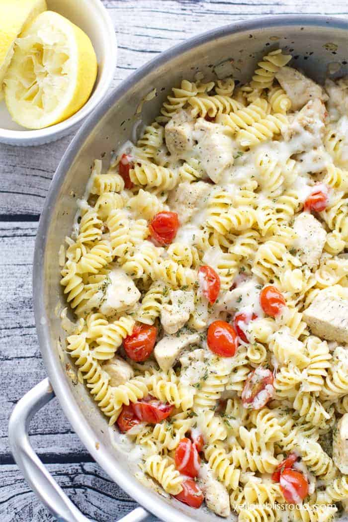 spicy lemon chicken pasta with tomatoes in large steel skillet