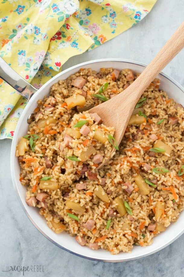 leftover ham and pineapple rice overhead in white pan with wooden spoon stuck in the pan