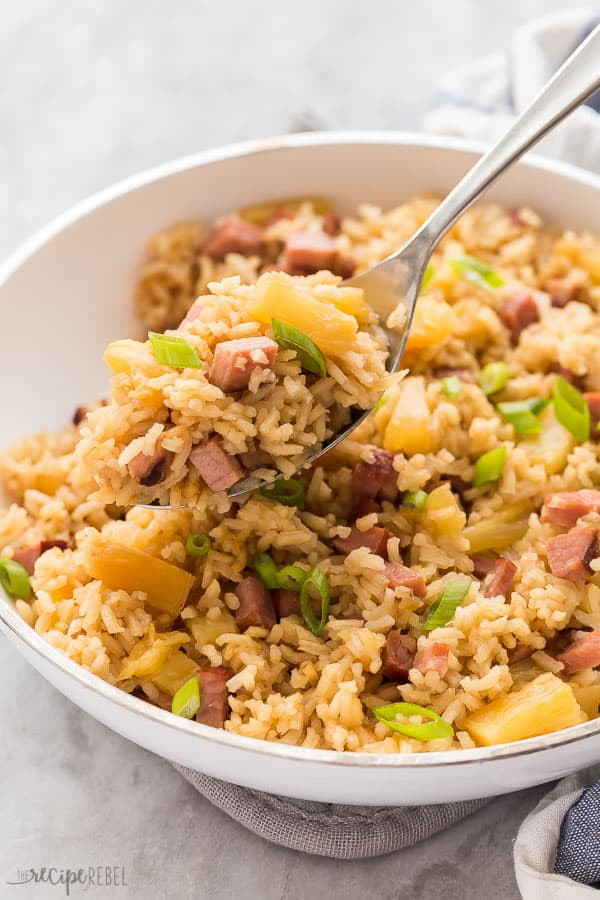 ham and pineapple rice scoop out of white pan on metal spoon