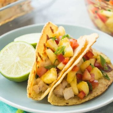 These Baked Hawaiian Chicken Tacos are perfect for game day or any gathering because you can serve a whole bunch at once! Stuffed with slow cooker coconut chicken, baked, then topped with an easy homemade pineapple salsa!