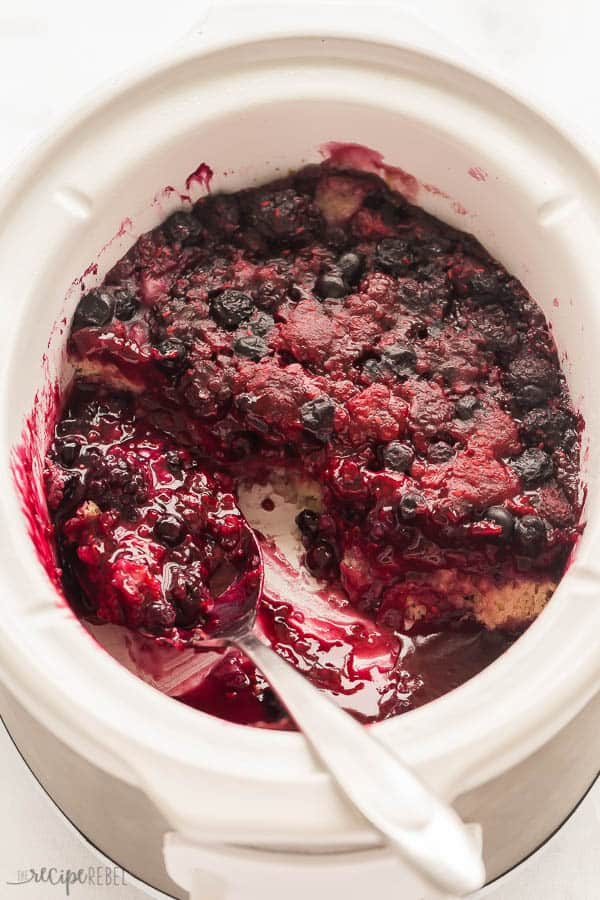 slow cooker berry cobbler in white crockpot with scoop missing