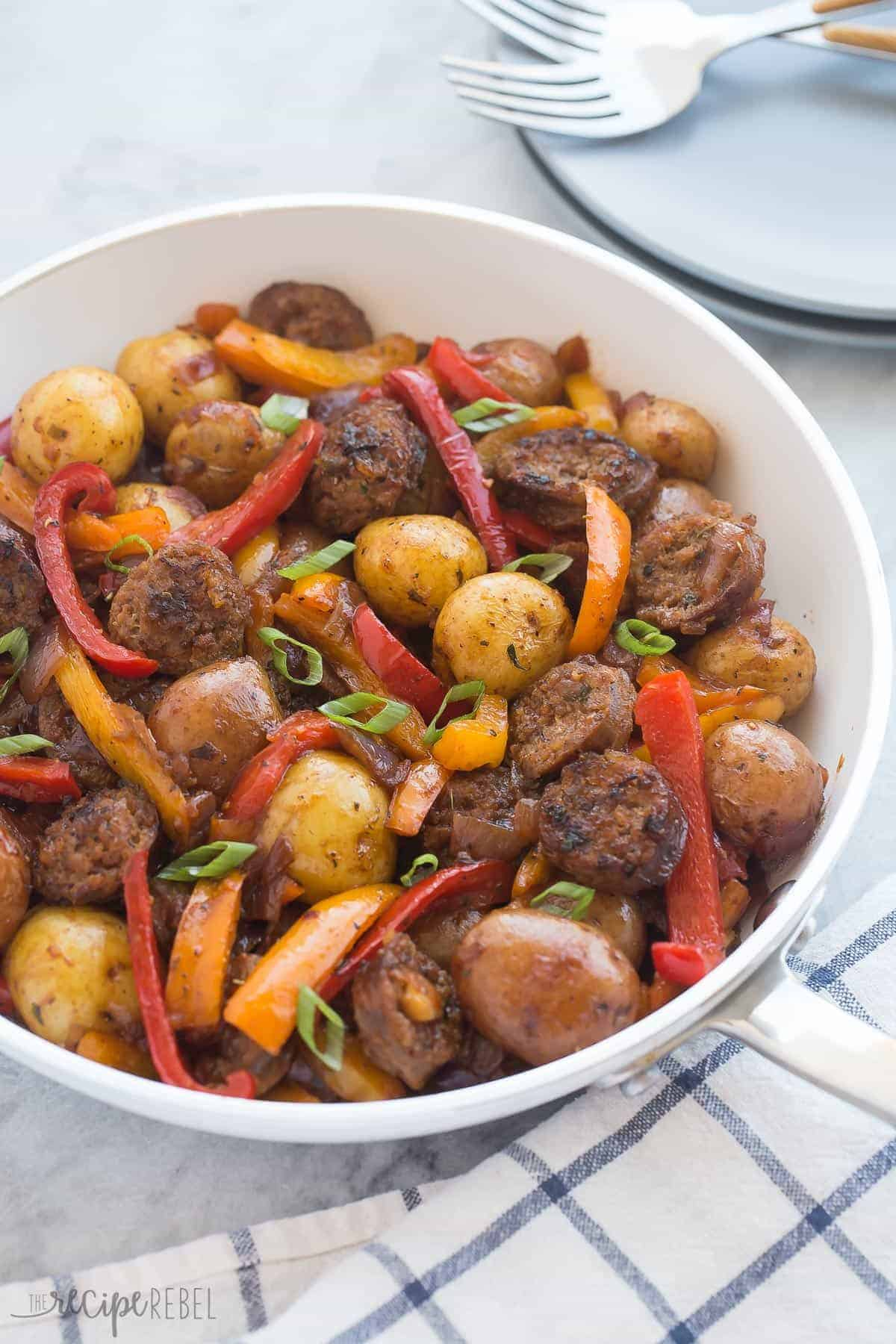 one pot sausage and peppers in white skillet with green onions