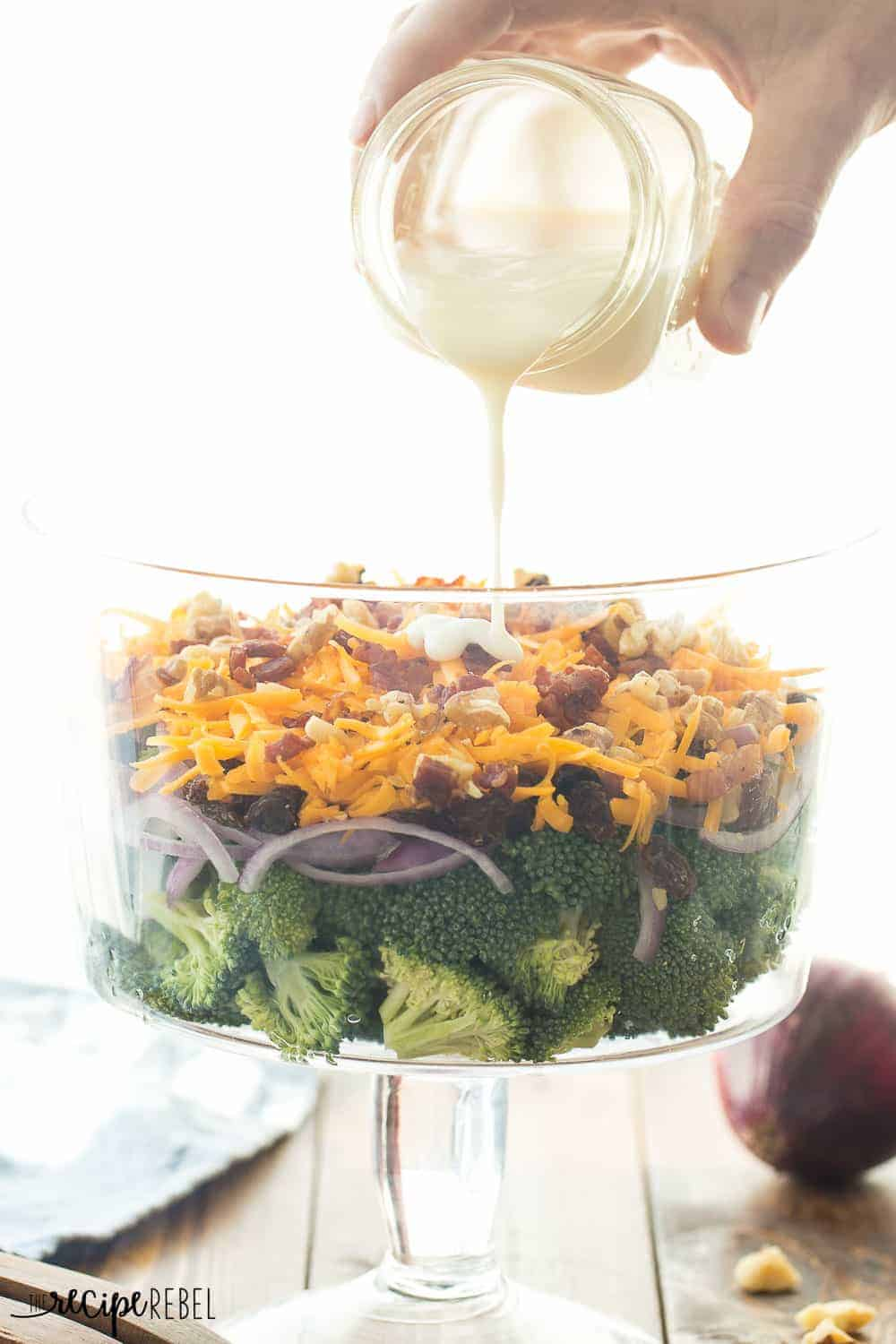 My husband's FAVORITE! This Layered Broccoli Salad is loaded with cheddar cheese, raisins, cranberries, bacon and walnuts and served with a sweet and tangy dressing!