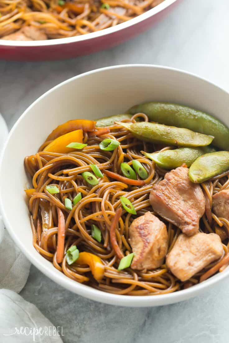 one pan teriyaki chicken and noodles in white bowl with peppers and snap peas