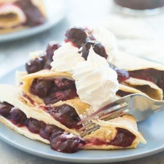These Cherry Cheesecake Crepes are filled with sweetened cream cheese and homemade cherry pie filling, then topped with whipped cream and extra cherries! They are perfect for dessert or a special breakfast or brunch!