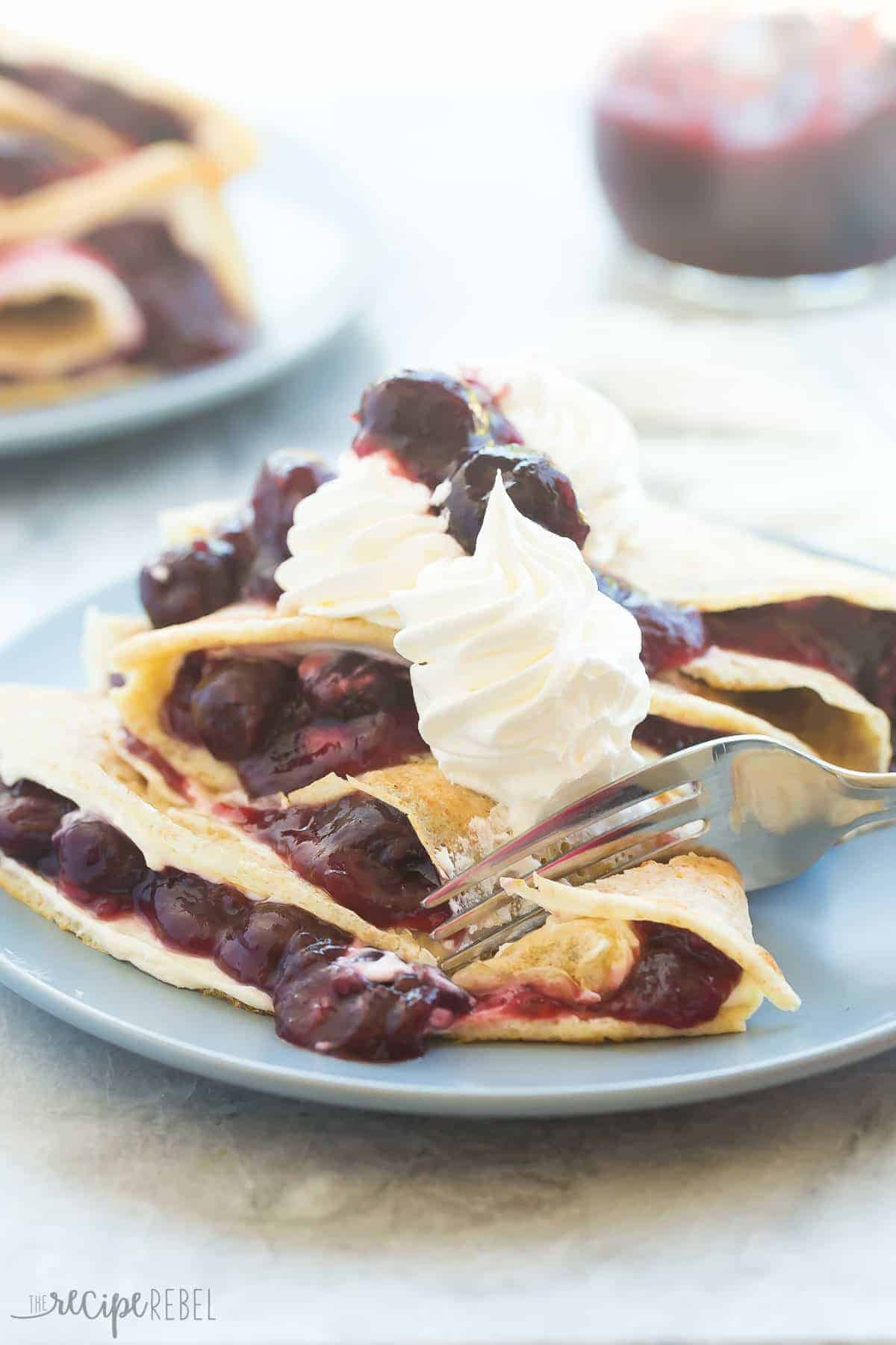 close up image of crepes folded with cream cheese and homemade cherry sauce topped with whipped cream