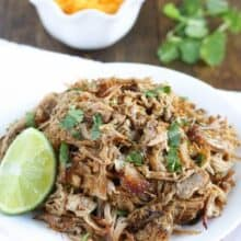 white plate filled with crockpot pork carnitas and lime wedge on side
