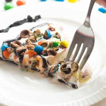 This Frozen Ice Cream Dessert Pizza is THE no bake summer dessert you need! A Dairy Queen Copycat Treatzza Pizza, it has an Oreo fudge crust topped with ice cream, fudge sauce and M&M's! https://www.thereciperebel.com/frozen-ice-cream-dessert-pizza-treatzza-pizza/