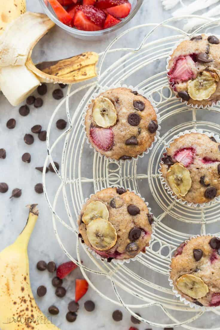 strawberry banana chocolate chip muffins overhead on white cooling rack with bananas strawberries and chocolate chips all around