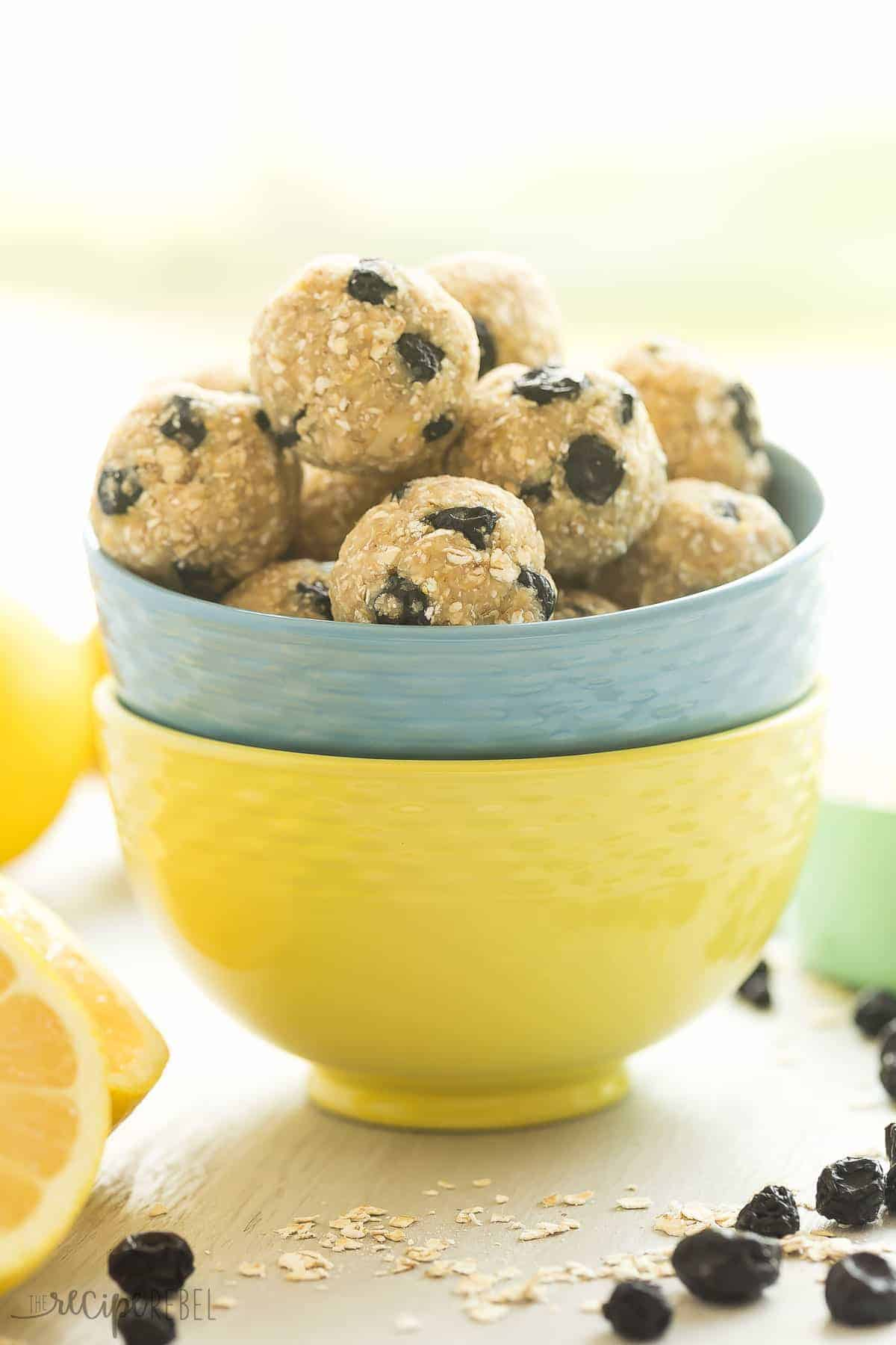 lemon blueberry energy bites in a blue bowl stacked in a yellow bowl