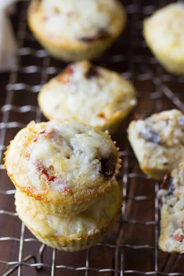 egg quinoa breakfast muffins two stacked on a cooling rack with more behind