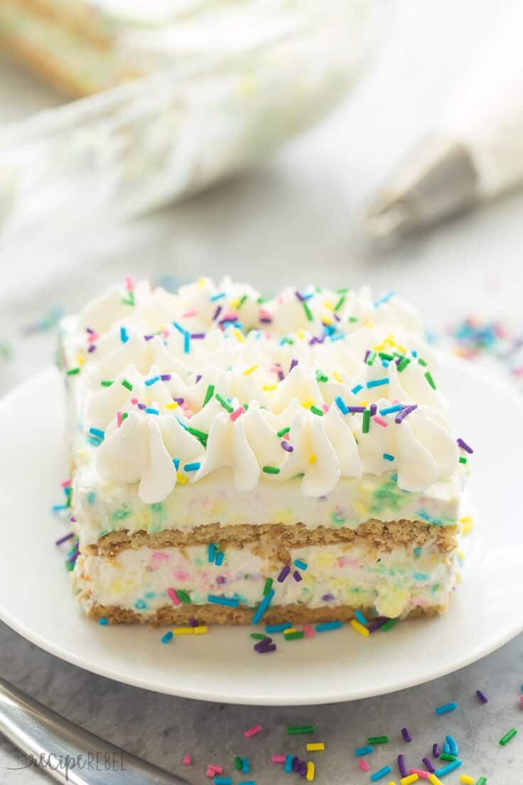 no bake funfetti icebox cake piece on white plate with lots of sprinkles