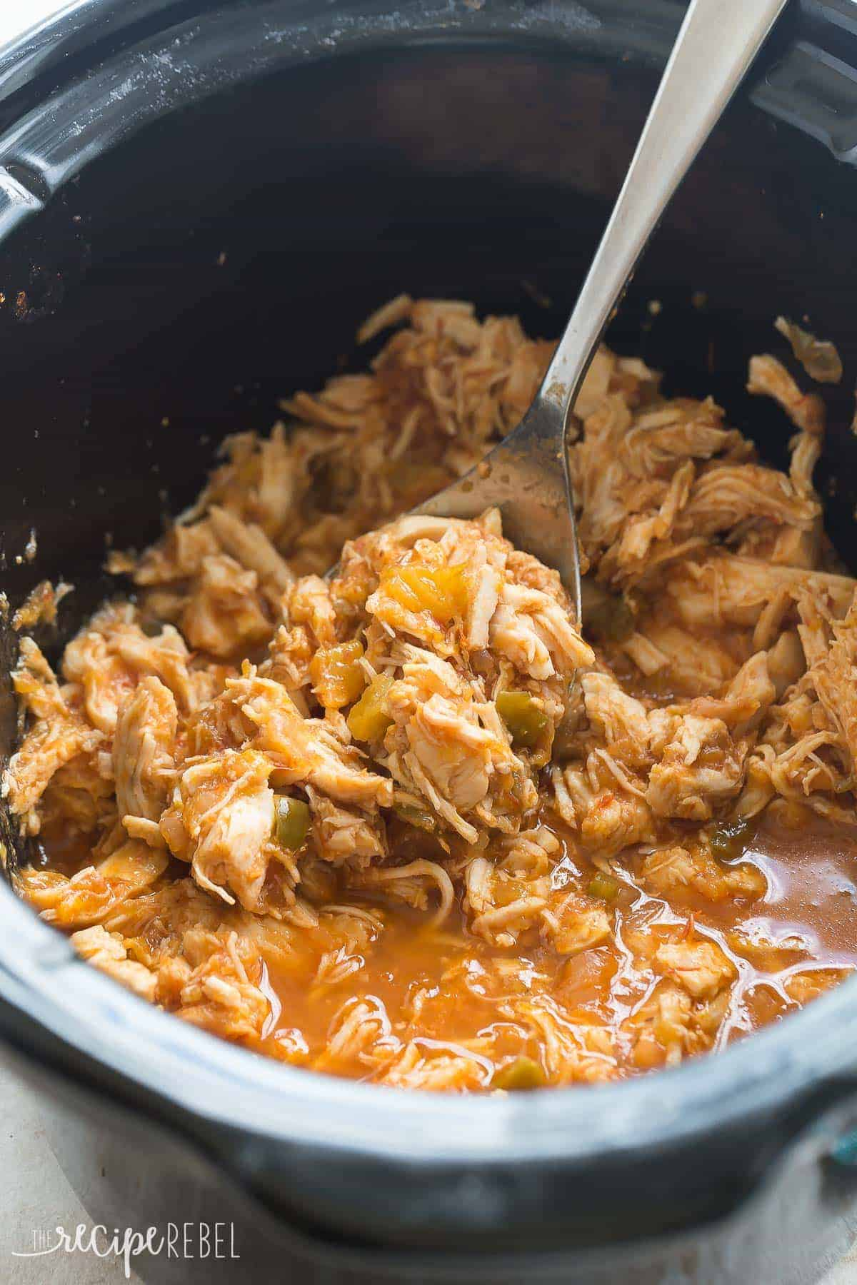 mango salsa chicken shredded in black slow cooker with metal scoop