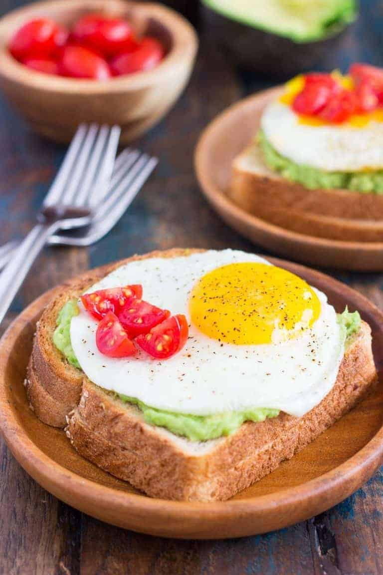 fried egg avocado toast with fresh cherry tomatoes and pepper