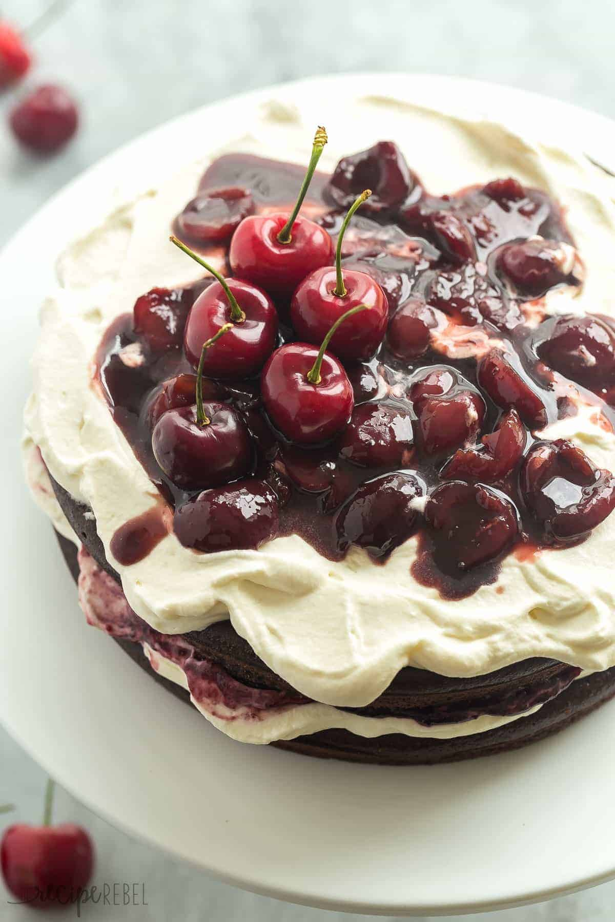 gluten free black forest cake whole with whipped cream and fresh dark cherry sauce