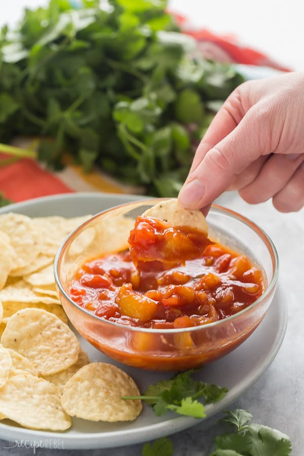 hand dipping chip in glass bowl with mango salsa