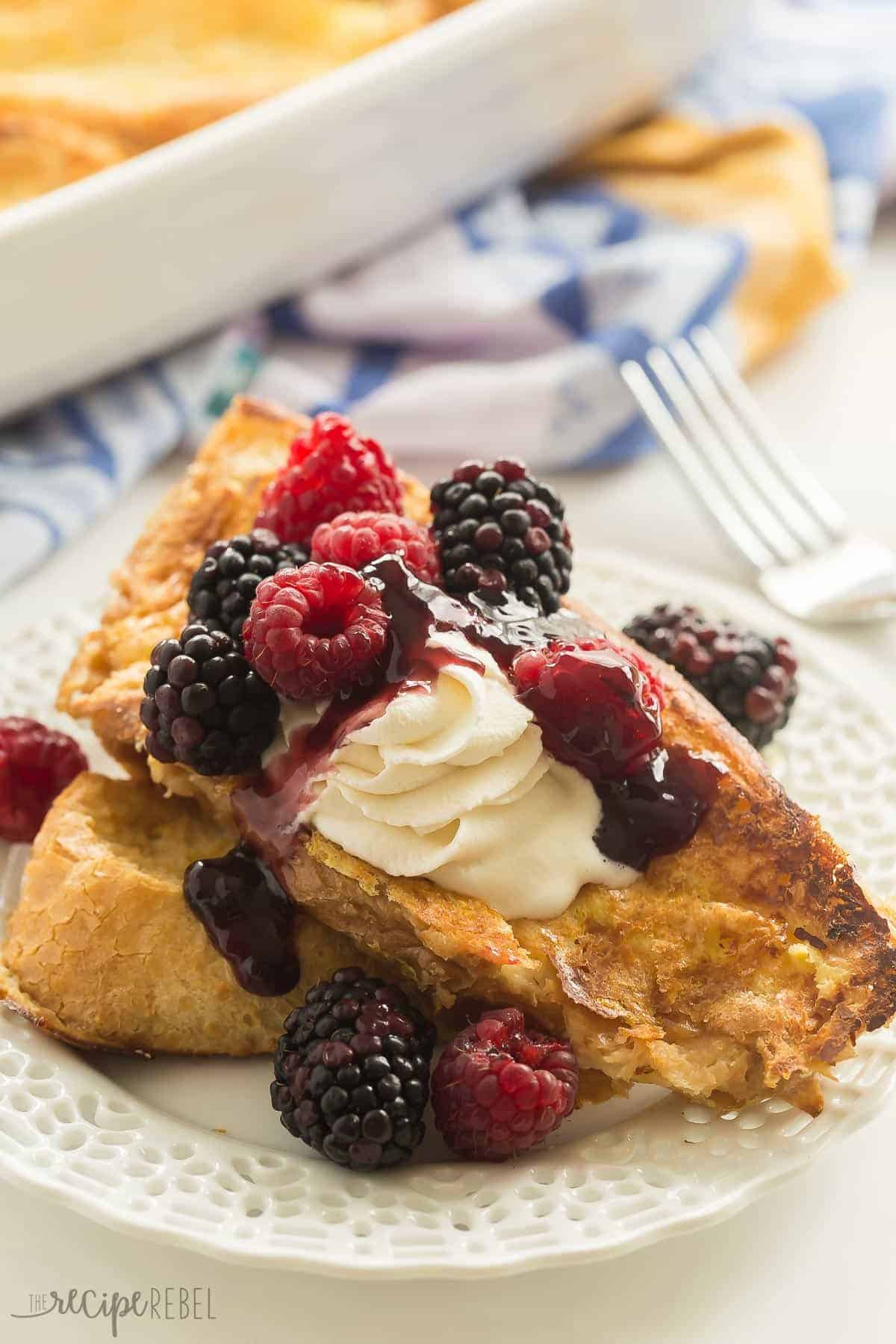 two pieces of lemon french toast stacked on white plate with whipped cream and berries