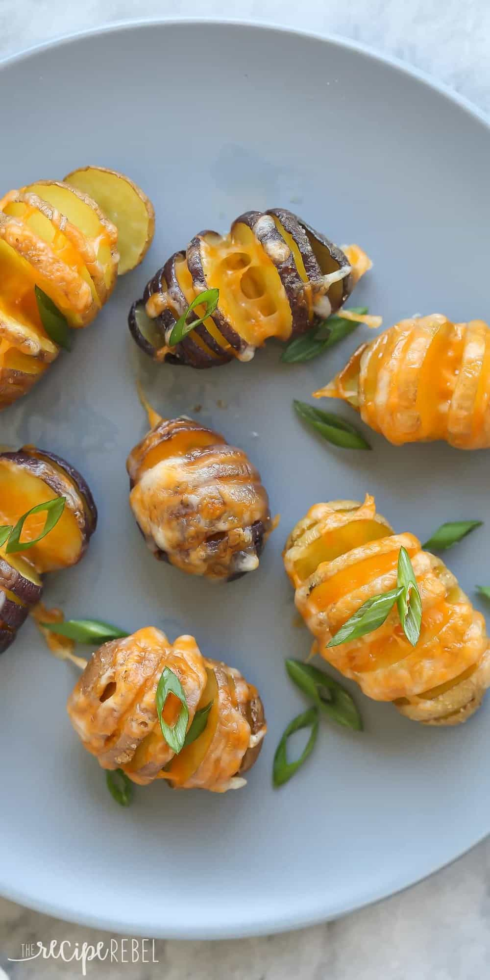 little cheesy hasselback potatoes overhead on grey plate with green onions