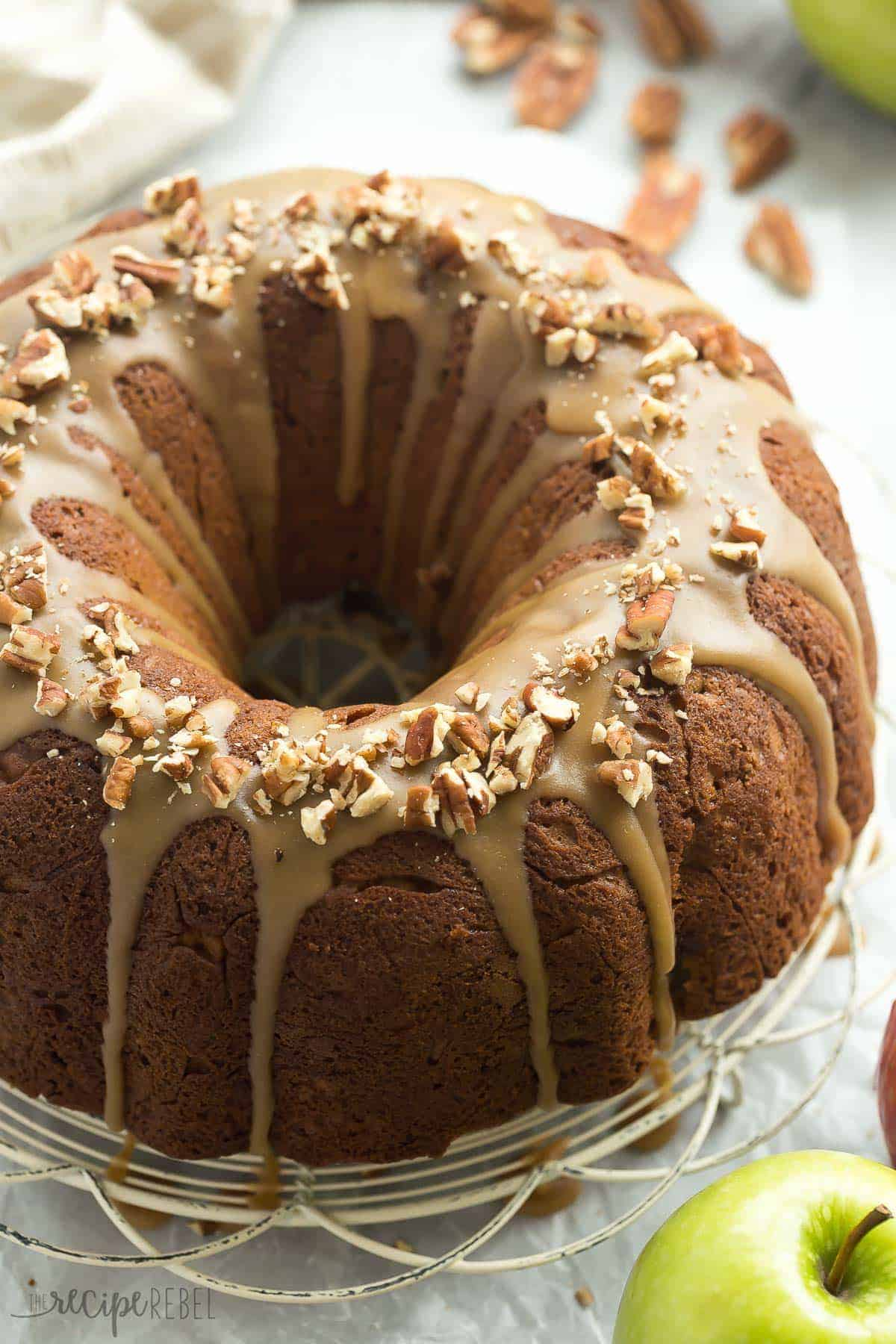 whole praline apple bundt cake on white cooling rack with praline glaze and pecans