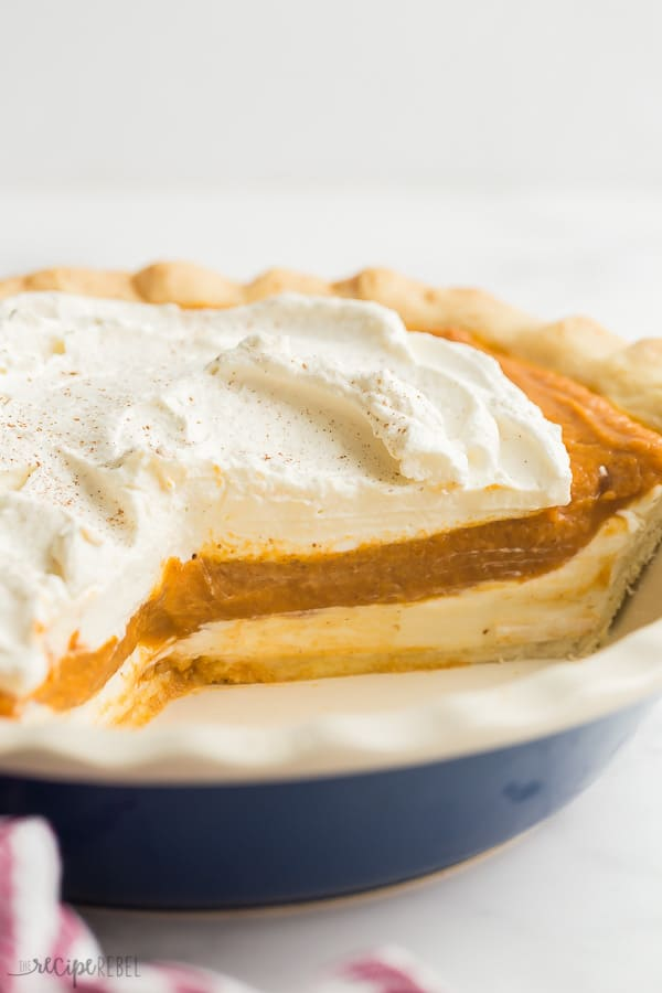 cream cheese pumpkin pie cut with pieces removed in blue pie plate