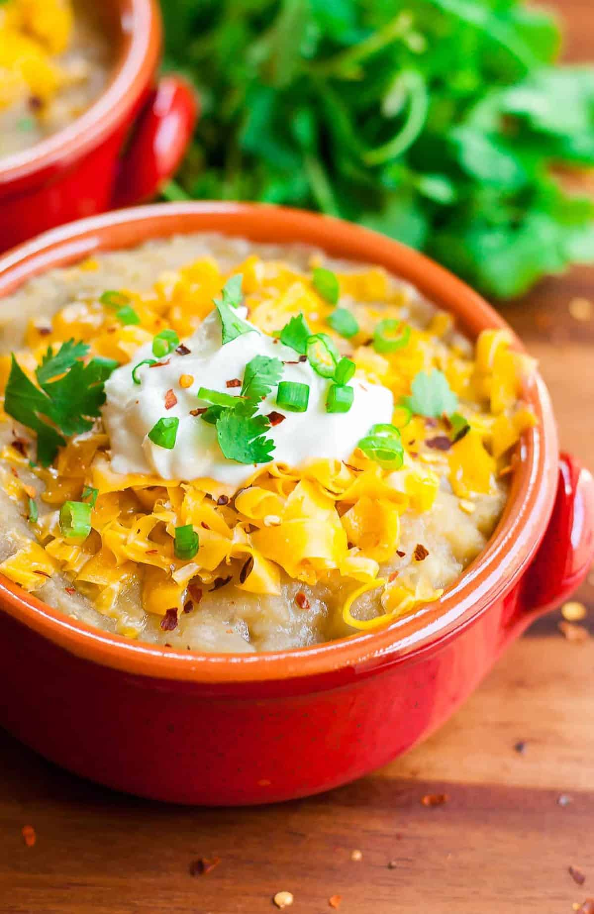 mexican baked potato soup in red bowl with shredded cheese sour cream and sliced green onions