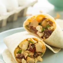 These are our FAVORITE Breakfast Burritos! They are loaded with homemade hashbrowns, peppers, bacon, eggs, salsa and cheese! They are make ahead and freezer friendly -- perfect for busy weeknights.