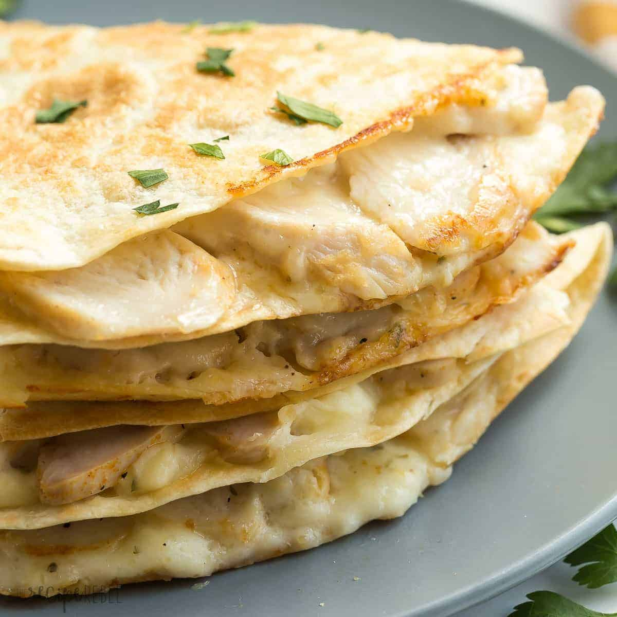 close up image of chicken alfredo quesadillas stacked on grey plate