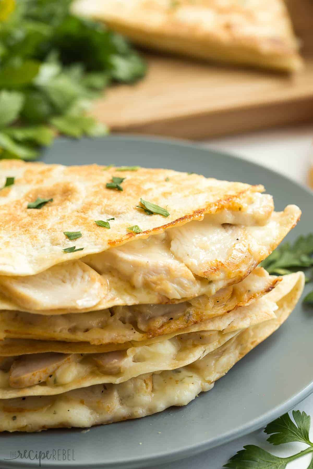 stack of chicken alfredo quesadillas on grey plate sprinkled with fresh parsley