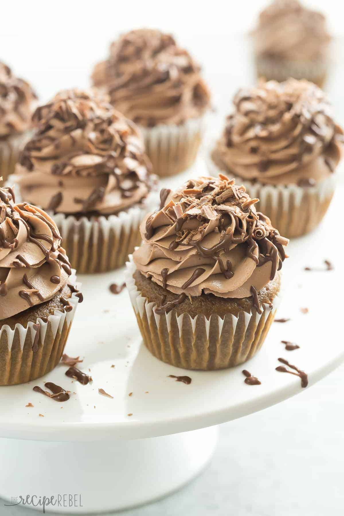 white cake plate full of mocha nutella cupcakes with frosting and chocolate drizzle