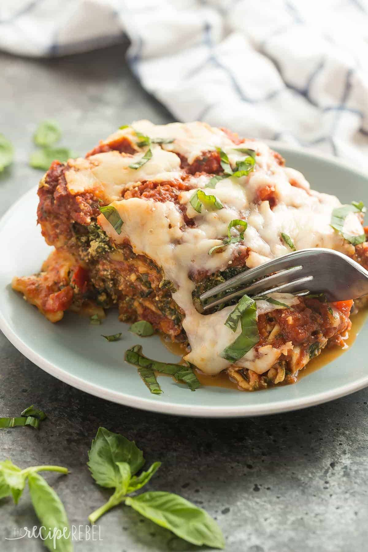 slow cooker spinach lasagna on blue plate with fork taking a bite