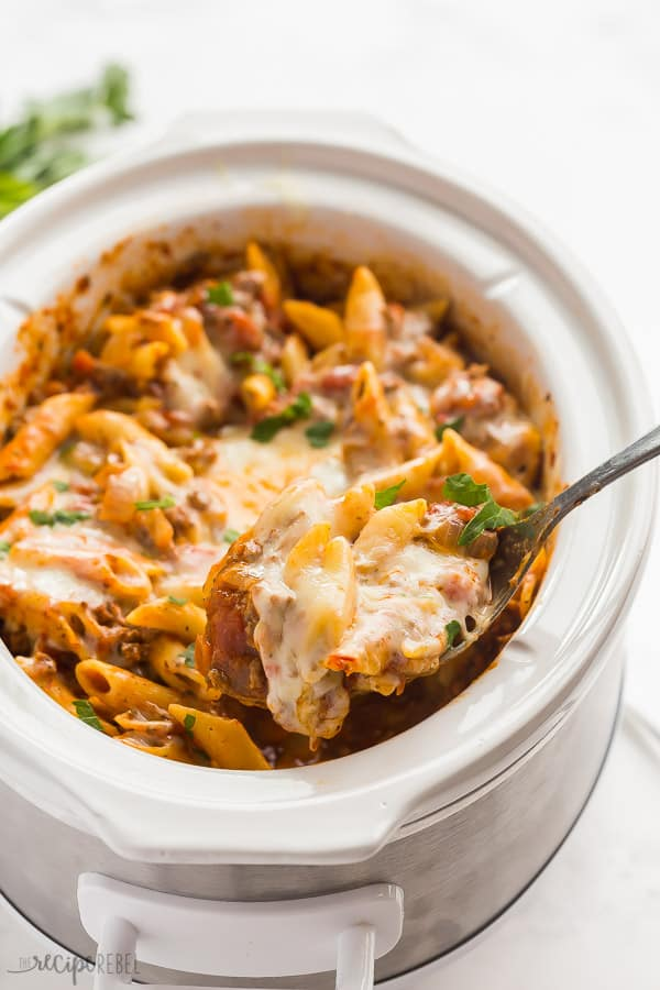 crock pot baked ziti in white slow cooker on white background with spoon scooping some
