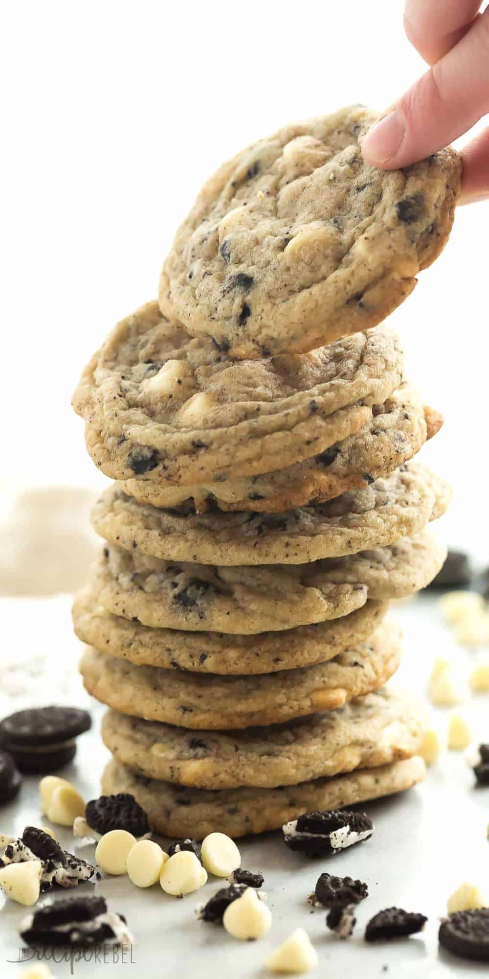 tall stack of cookies and cream cookies with white chocolate chips and crushed oreos on a white background