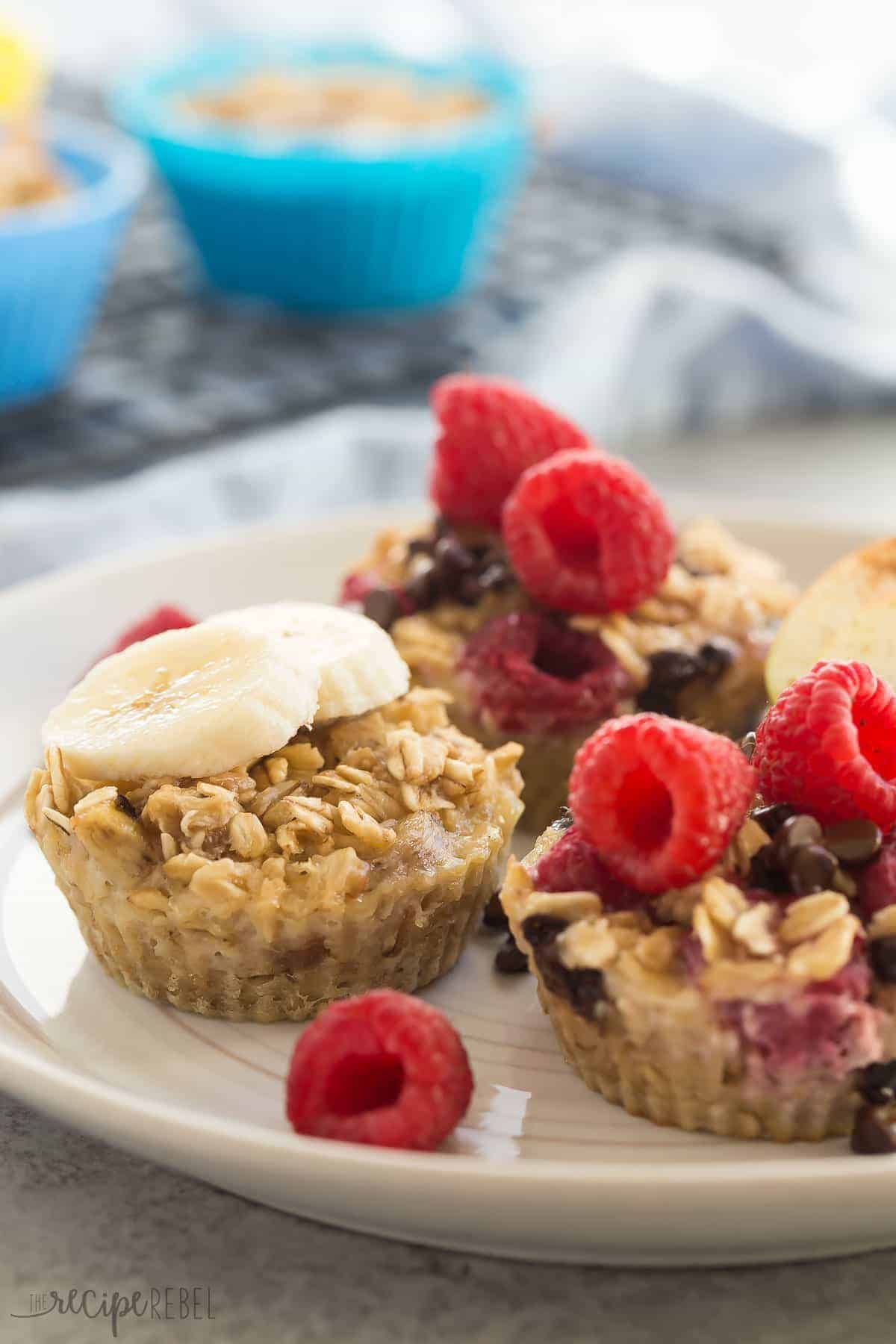 four ingredient oatmeal cups on a white plate with banana slices and raspberries and extra in the background