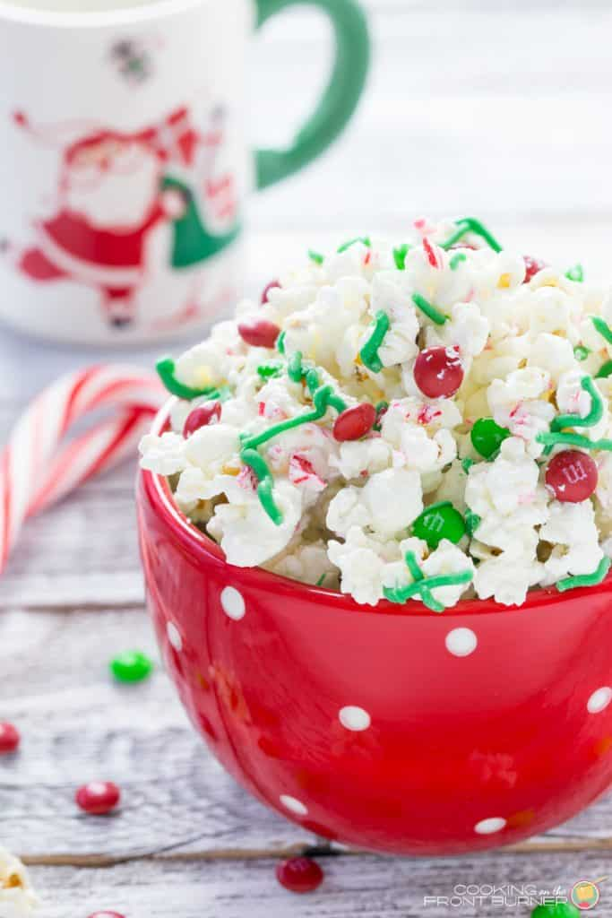 white chocolate peppermint popcorn piled high in red bowl with christmas M&Ms