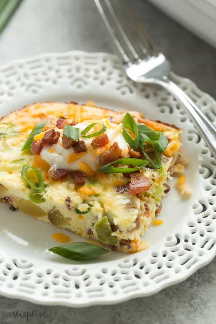 loaded baked potato breakfast casserole piece on white plate with sour cream and green onions