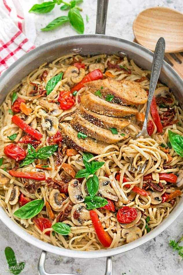 stainless steel pan with linguine and sliced chicken breast peppers tomato and basil